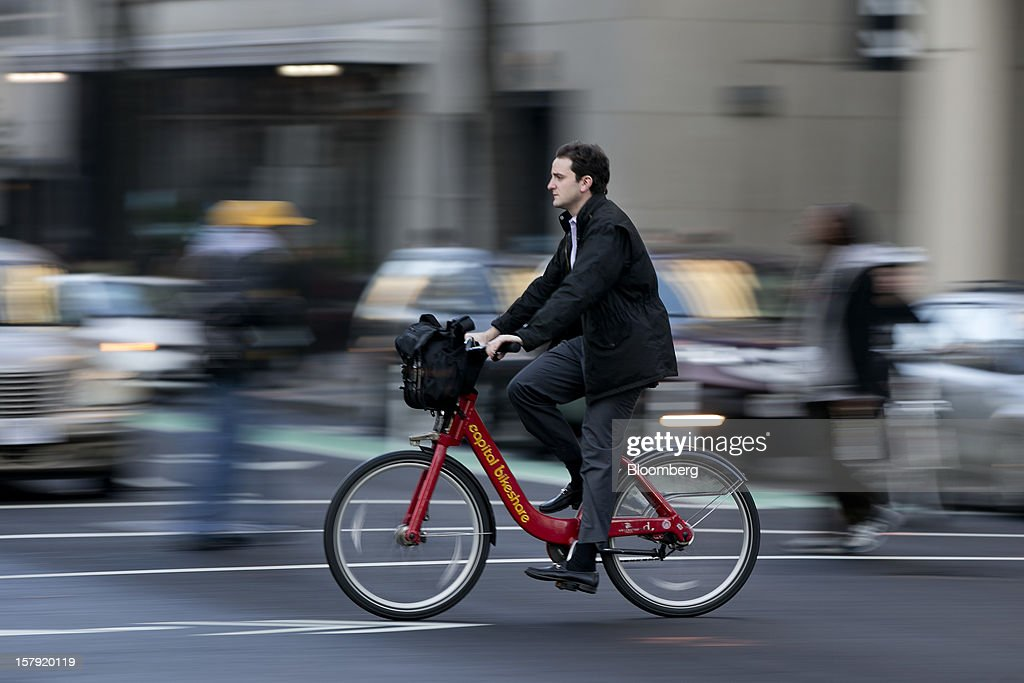 A Capital Bikeshare bicyclist rides on a bike lane in Washington, D.C., U.S., on Monday, Dec. 3, 2012. Since Sept. 2010, Capital Bikeshare has dispersed more than 1700 bikes for rent across the city and has totaled over 3.5 million rides since Sept. 2011. Alta Bicycle Share, the company that was awarded the contract to run the program, has installed 191 solar-powered docking stations throughout the District and Arlington, Virginia. Photographer: Andrew Harrer/Bloomberg via Getty Images