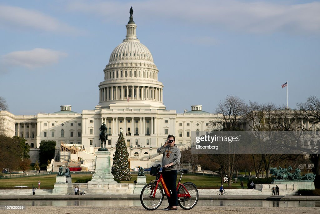 A Capital Bikeshare bicyclist takes a photograph in front of the U.S. Capitol in Washington, D.C., U.S., on Monday, Dec. 3, 2012. Since Sept. 2010, Capital Bikeshare has dispersed more than 1700 bikes for rent across the city and has totaled over 3.5 million rides since Sept. 2011. Alta Bicycle Share, the company that was awarded the contract to run the program, has installed 191 solar-powered docking stations throughout the District and Arlington, Virginia. Photographer: Andrew Harrer/Bloomberg via Getty Images