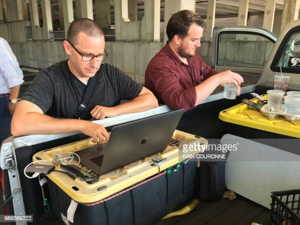 TOPSHOT Capital Gazette reporter Chase Cook and photographer Joshua McKerrow work on the next days newspaper while awaiting news from their...