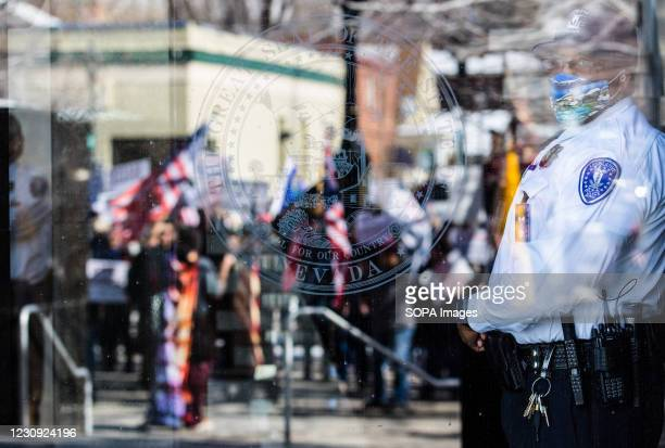 Capital police officer looks on behind the glass at the states legislative building Protesters gathered at the state's legislative building to...