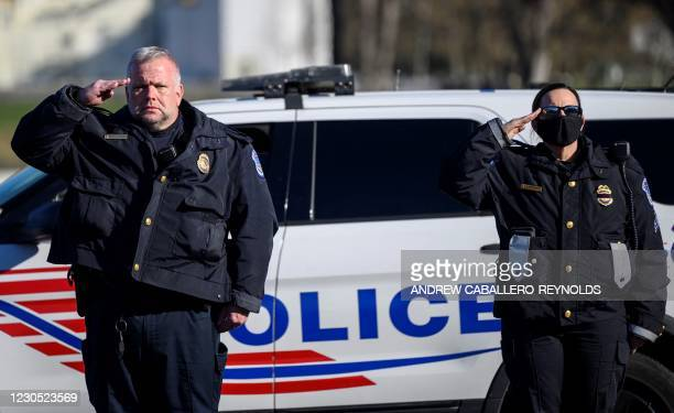 Capital police officers salute as the casket with fallen police officer, Brian Sicknick, passes during a funeral procession in Washington, DC on...