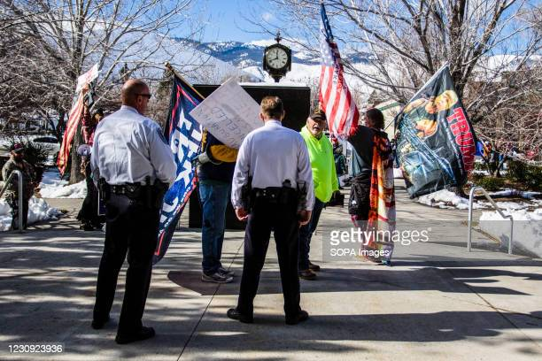 Capital police officers watch protestors holding flags during the demonstration. Protesters gathered at the state's legislative building to protest...