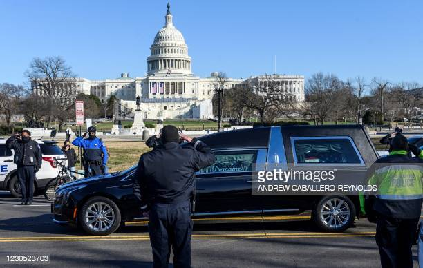 Capital police salute as the casket with fallen police officer, Brian Sicknick, passes during a funeral procession in Washington, DC on January 10,...