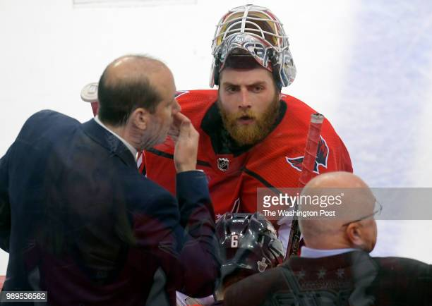 Capitals assistant coach Todd Reirden left talks to goaltender Braden Holtby during a time out To the right is head coach Barry Trotz during the...