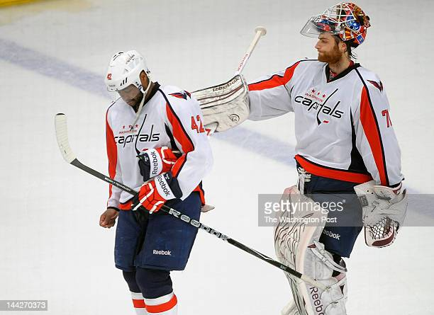 Capitals' Joel Ward left gets a pat on the back from goalie Braden Holtby right as they exit the ice after the New York Rangers defeat the Washington...