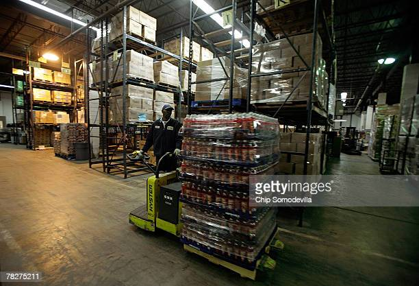 Capitol Area Food Bank employee uses an electric dolly to move a pallate of soda at the bank December 5 2007 in Washington DC Many food banks and...