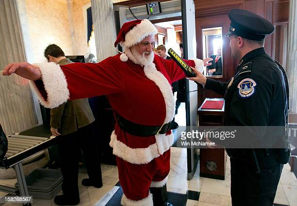 Capitol Hill police check an unidentified man dressed as Santa Claus with a metal detector as he enters the US Capitol on his way to Speaker of the...