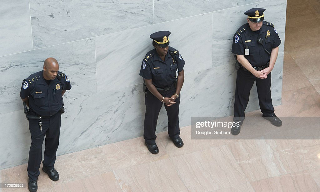 U.S. Capitol Hill Police keep an eye on immigration protesters in the Senate Hart Office Building atrium on June 18, 2013.