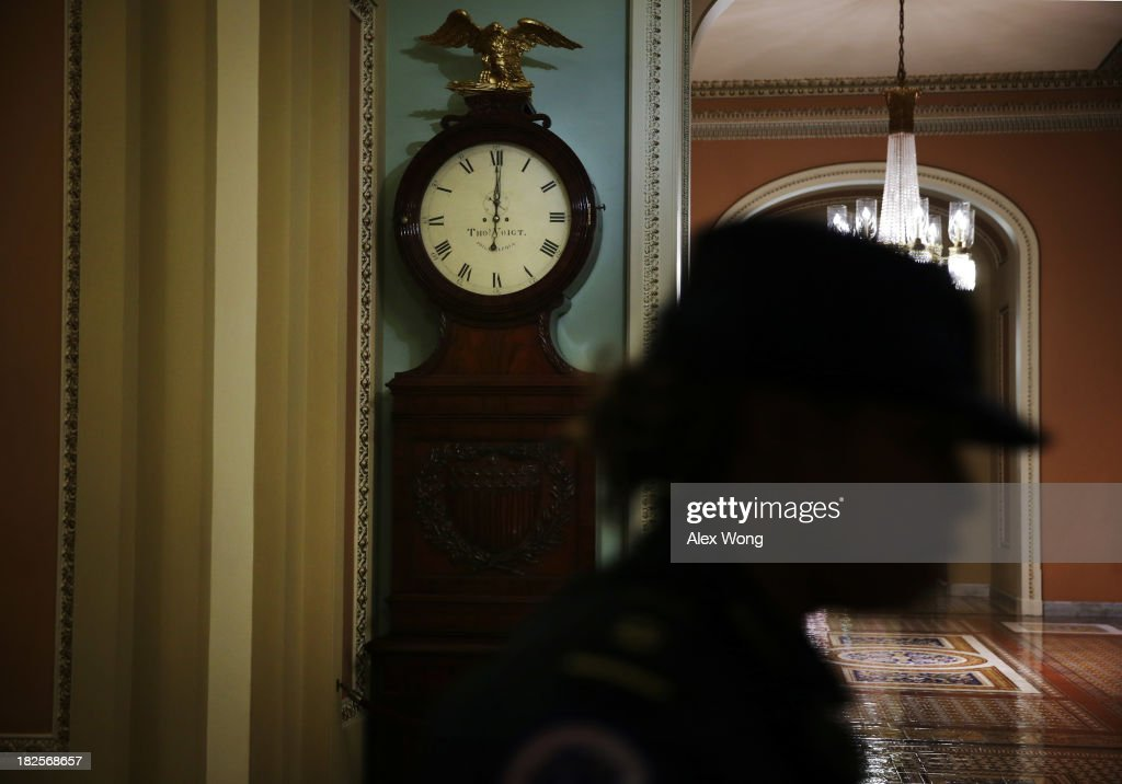 A Capitol Hill Police officer passes by the Ohio Clock which shows the time has just passed midnight on the Senate side of the U.S. Capitol October 1, 2013 on Capitol Hill in Washington, DC. The U.S. government was officially shut down after the Senate and the House of the Representatives failed to come to an agreement to pass a federal spending bill to keep the government running.