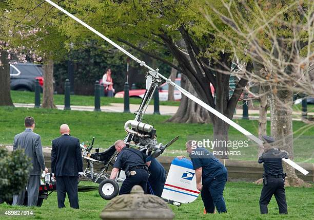 Capitol Hill police officers and other officials lift a gyrocopter that landed on the US Capitol South Lawn on to a trailer April 15 in Washington DC...