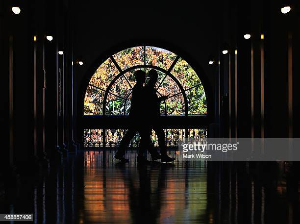 Capitol hill staff members walk past a window showing colorful fall leaves, inside the Russell Senate Office Building, November 12, 2014 in...