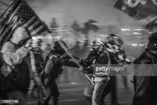 Image was converted to black and white) Capitol Police and MPD used physical force and tear gas to force the Trump supporters further away from the...