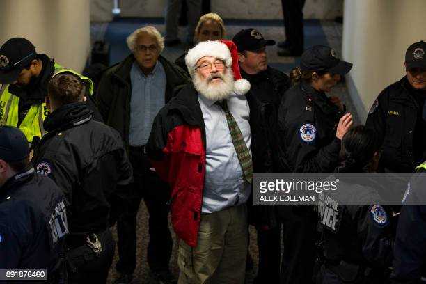 US Capitol Police arrest a demonstrator dressed as Santa Claus for participating in a sitin during a demonstration against Republican tax reform...