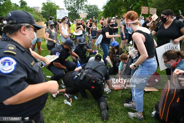 US Capitol Police help an overheated protestor as people protest the death of George Floyd on the East Lawn of the US Capitol on June 3 in Washington...