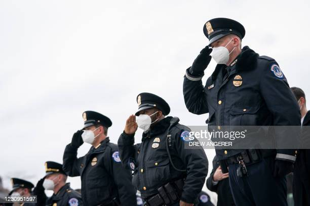 Capitol Police honor guard salute as the remains of Officer Brian Sicknick are carried down the steps of the Capitol after laying in honor in the...