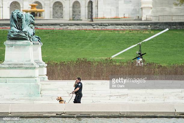 S Capitol Police officer and his dog sweep the area around the reflecting pool on the west front of the Capitol after a man was arrested for landing...