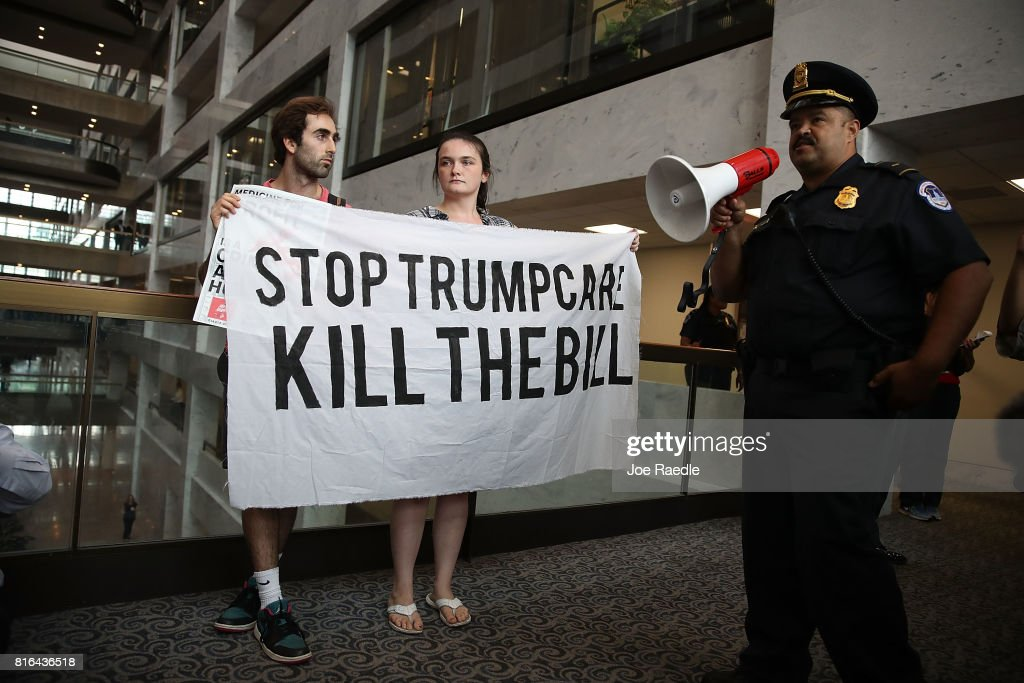 A U.S. Capitol Police officer asks protesters to leave the area around the office of Sen. Dean Heller (R-NV) as they voice their opinion about the proposed health care bill in the Hart Senate Office Building on July 17, 2017 in Washington, DC. Capitol Police arrested several protesters at various Senate offices as they asked Senators to vote no on the Better Care Reconciliation Act.