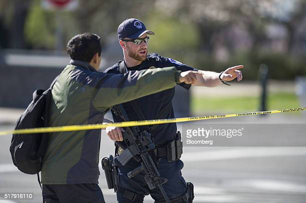 A US Capitol police officer directs a pedestrian to a detour after shots were fired at the visitor's center of the Capitol building in Washington DC...