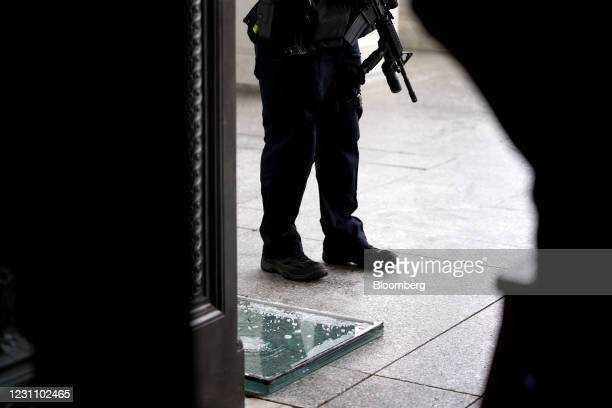 Capitol Police Officer holds a gun while standing near a window that had been broken in the January 6 riots as it lies on the ground at the U.S....