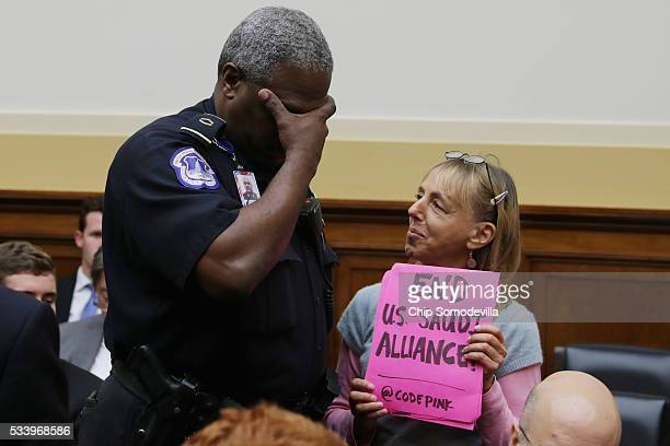 S Capitol Police officer humorously reacts to Code Pink for Peace activist Medea Benjamin's protest sign before a hearing of the House Foreign...