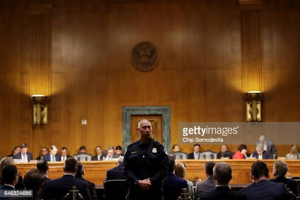 S Capitol Police officer keeps an eye on the public seating as former US Senator Dan Coats testifies during his confirmation hearing before the...