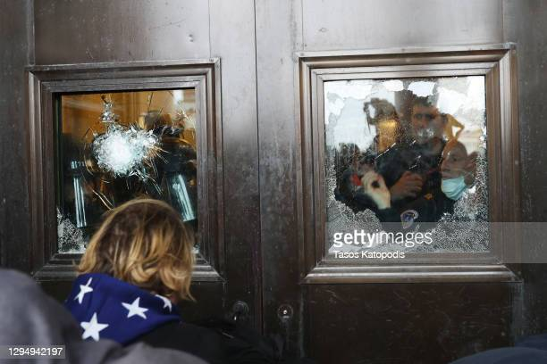 Capitol police officer looks out of a broken window as protesters gather on the U.S. Capitol Building on January 06, 2021 in Washington, DC....