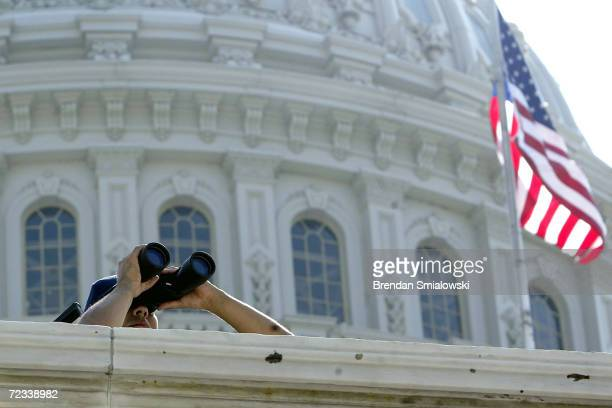 Capitol Police Officer looks out over the US capitol grounds with binoculars August 4 2004 in Washington DC Security around the US capitol has been...