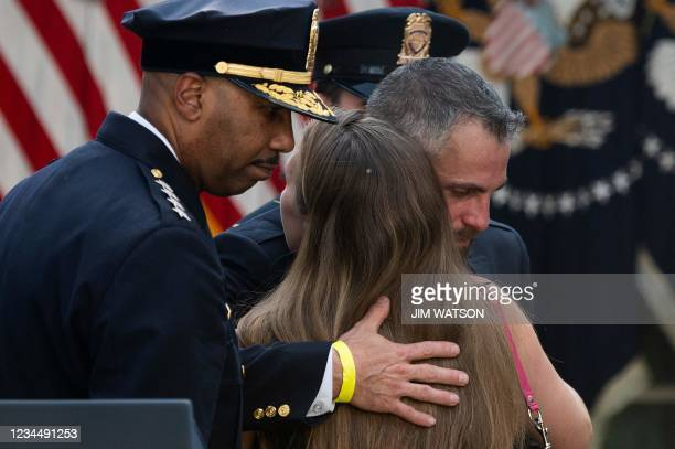 """Capitol Police Officer Michael Fanone hugs Shannon Terranova, ex-wife of late USCP Officer William """"Billy"""" Evans, at the White House in Washington,..."""