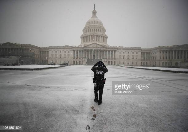 S Capitol Police Officer patrols the Capitol plaza as snow falls on November 15 2018 in Washington DC A winter storm advisory has been issued for the...