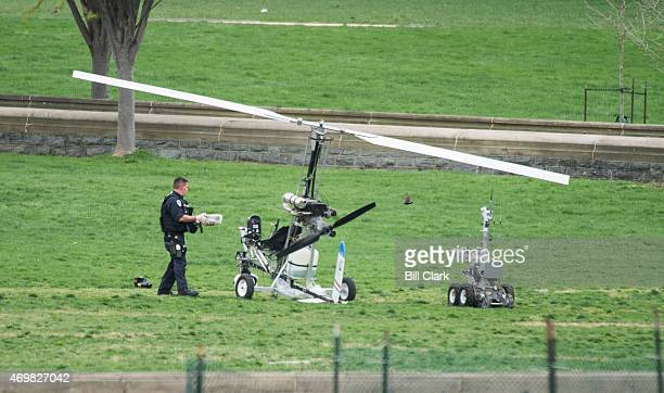 S Capitol Police officer removes a package from the undercarriage of the gyrocopter on the West Lawn of the US Capitol on Wednesday April 15 2015 The...