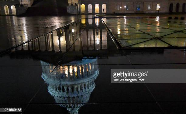 S Capitol Police officer stands guard at the US Capitol building in the rain late Thursday night The Capitol is reflected in the granite near the...