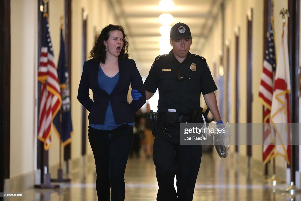 A U.S. Capitol Police officer walks with a health care protester that was arrested near the office of Sen. Mitch McConnell (R-KY) in the Russell Senate Office Building on July 17, 2017 in Washington, DC. Capitol Police arrested several protesters at various Senate offices as the protesters asked Senators to vote no on the Better Care Reconciliation Act.