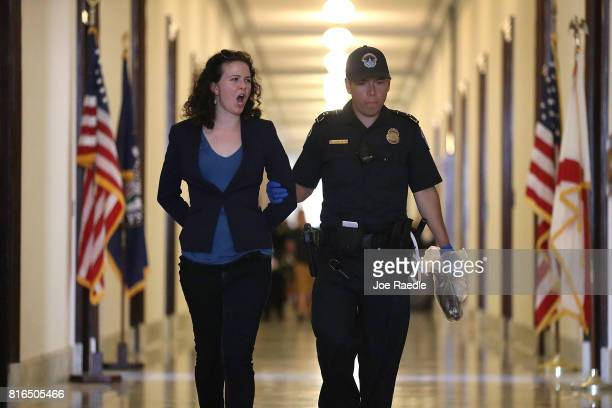 Capitol Police officer walks with a health care protester that was arrested near the office of Sen. Mitch McConnell in the Russell Senate Office...