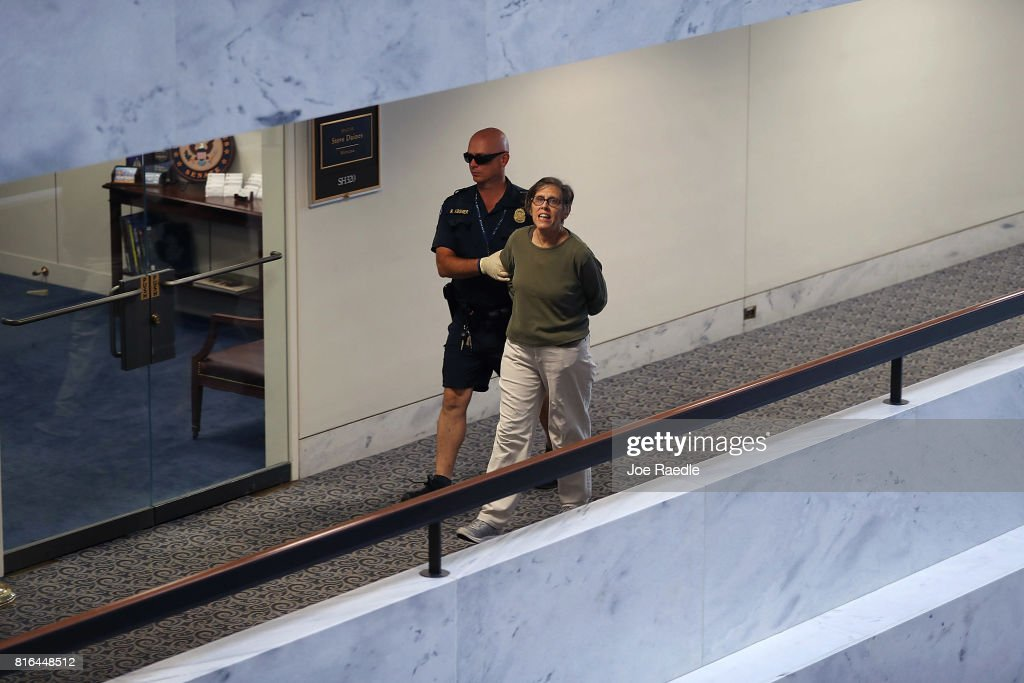 S. Capitol Police officer walks with an arrested protester near the office of Sen. Dean Heller (R-NV) in the Hart Senate Office Building on July 17, 2017 in Washington, DC. Capitol Police arrested several protesters at various Senate offices as the protesters asked Senators to vote no on the Better Care Reconciliation Act.