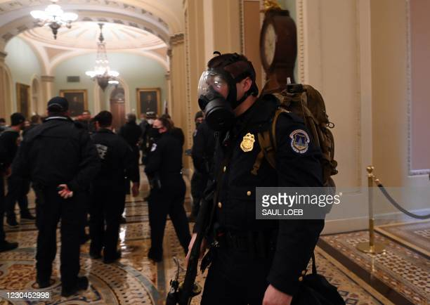 Capitol police officer wears a gas mask as supporters of US President Donald Trump enter the Capitol on January 6 in Washington, DC. - Demonstrators...