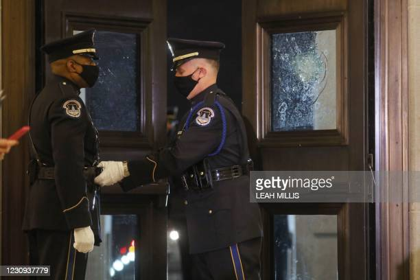 Capitol Police Officers adjust each other's uniforms at the entrance of the US Capitol Rotunda where fellow officer Brian Sicknick will lie in honor...
