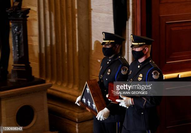 Capitol Police Officers carry the urn holding the remains of fellow officer Brian Sicknick and a US flag to lie in honor in the Capitol Rotunda in...