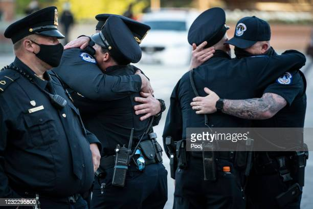 Capitol Police officers embrace after the casket of Officer William Evans departed after lying in honor in the Capitol Rotunda on April 13, 2021 in...