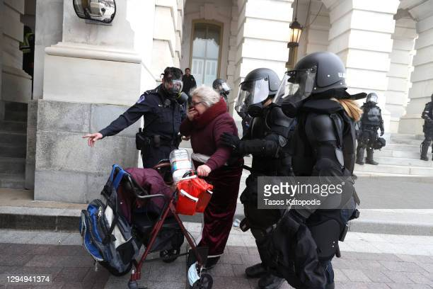 Capitol police officers help a woman as protesters gather on the U.S. Capitol Building on January 06, 2021 in Washington, DC. Pro-Trump protesters...