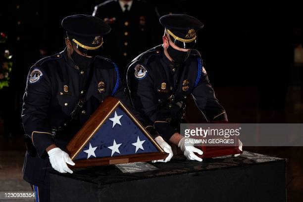 Capitol Police Officers place the urn holding the remains of fellow officer Brian Sicknick on a stand to lie in honor in the Capitol Rotunda in...