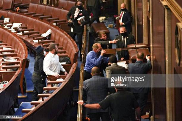 Capitol police officers point guns at a door during a joint session of Congress to count the votes of the 2020 presidential election takes place in...