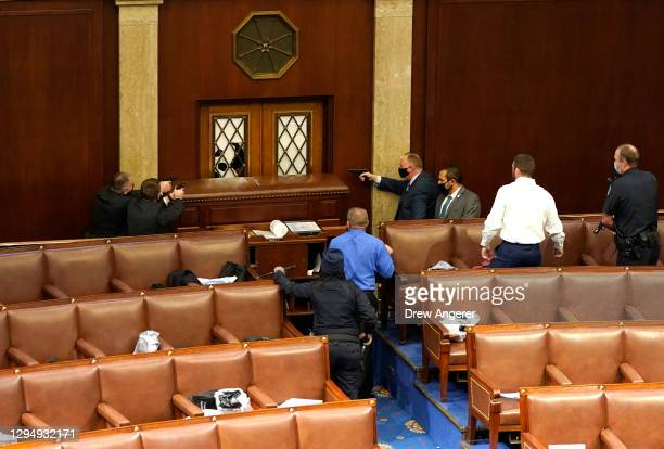 Capitol police officers point their guns at a door that was vandalized in the House Chamber during a joint session of Congress on January 06, 2021 in...