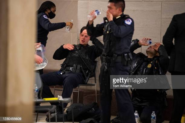Capitol Police officers receive medical treatment after clashes with protesters attempting to disrupt the joint session of Congress to certify the...