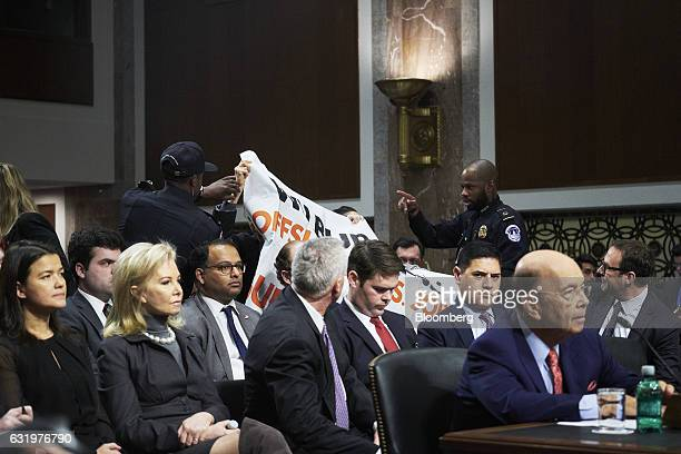 US Capitol police officers remove protesters as billionaire investor Wilbur Ross commerce secretary nominee for US Presidentelect Donald Trump pauses...