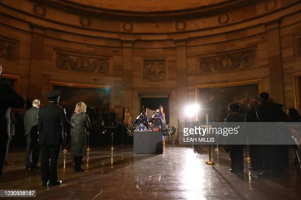 Capitol Police Officers salute after placing on a stand the urn holding the remains of fellow officer Brian Sicknick to lie in honor in the Capitol...