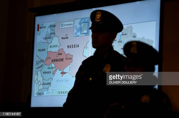 US Capitol police officers stand in front of a TV screen during the first public impeachment hearing on the inquiry into US President Donald J Trump...