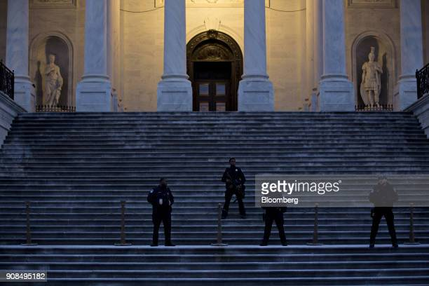 US Capitol police officers stand outside the Capitol in Washington DC US on Sunday Jan 21 2018 The House and Senate are back in session Sunday with a...