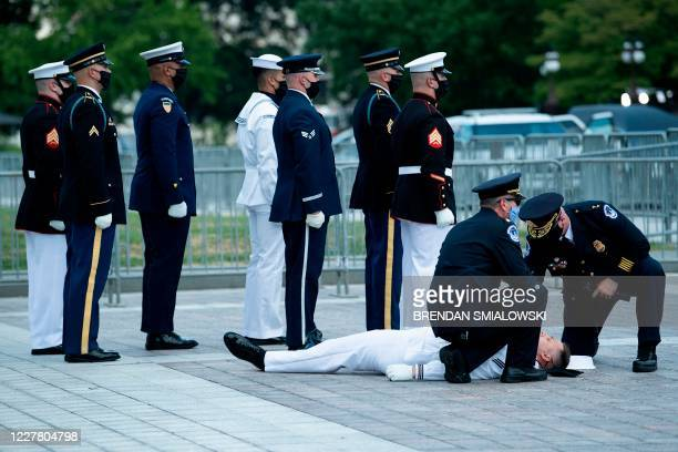 Capitol Police officers tend to a member of the joint services military honor guard who collapsed in the heat before carrying the flag-draped casket...