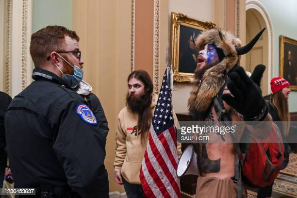 Capitol police officers try to stop supporters of US President Donald Trump, including Jake Angeli , a QAnon supporter known for his painted face and...