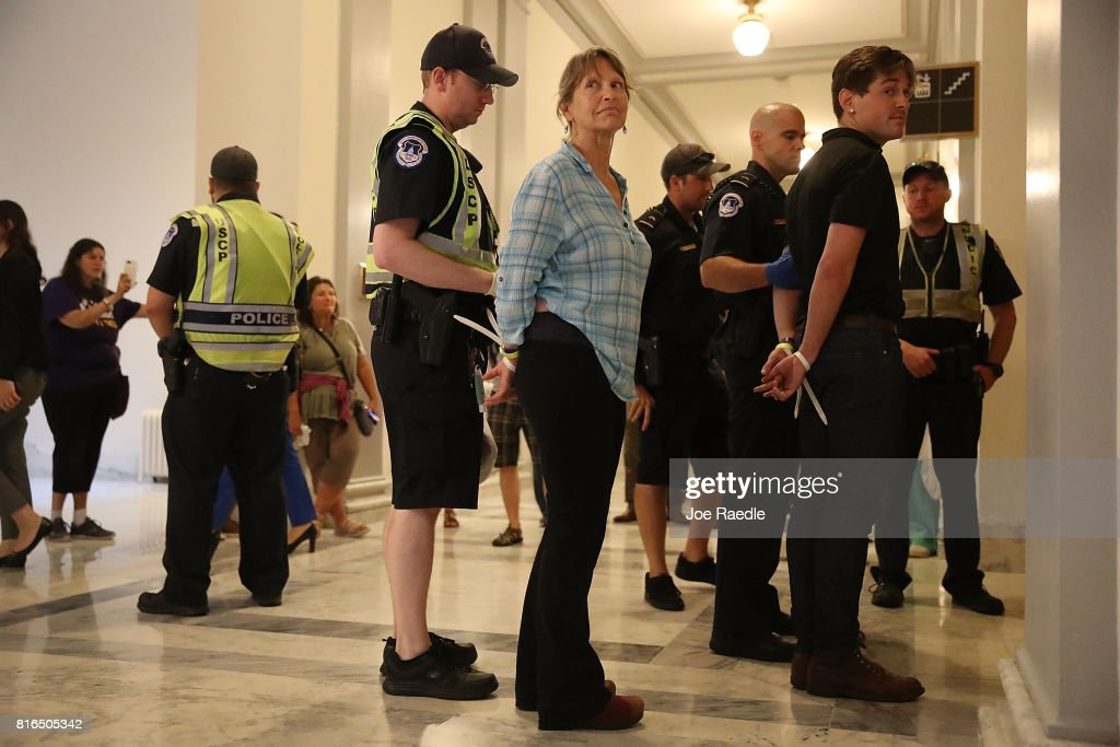 U.S. Capitol Police officers walk with protesters arrested near the office of Sen. Mitch McConnell (R-KY) in the Russell Senate Office Building on July 17, 2017 in Washington, DC. Capitol Police arrested several protesters at various Senate offices as the protesters asked Senators to vote no on the Better Care Reconciliation Act.